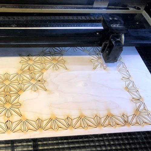 Wood on laser bed being engraved