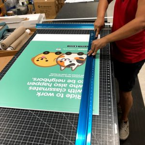 hands cutting out a sign